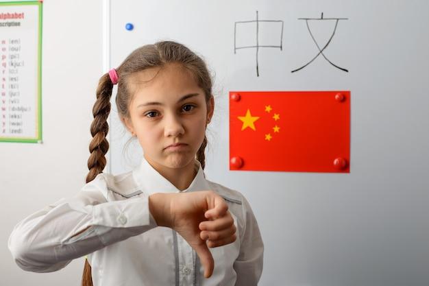 Piccolo studente di scuola in piedi in classe con la bandiera cinese sul tabellone che mostra i pollici verso il basso