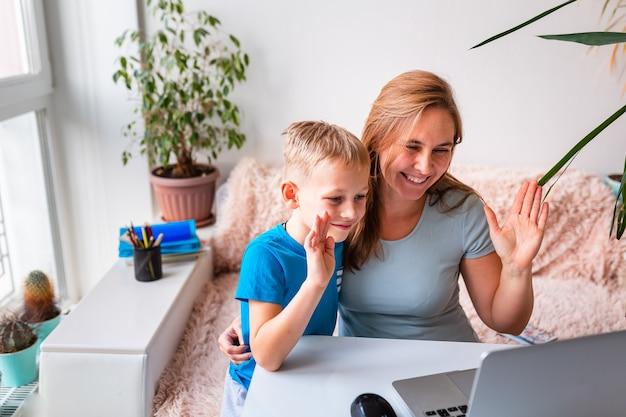 Piccolo scolaro che studia a casa con un computer portatile