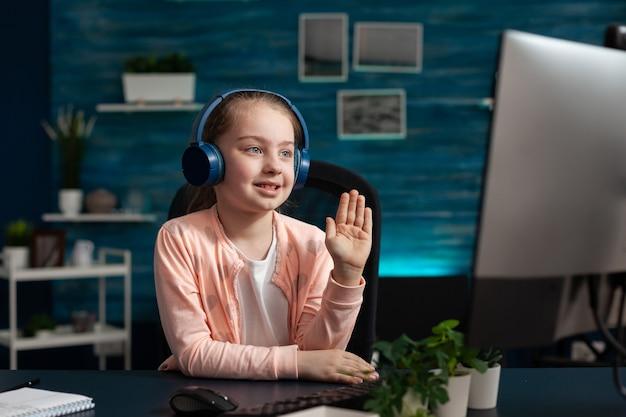 Piccolo scolaro che indossa l'auricolare saluta l'insegnante remoto durante il videocalo online