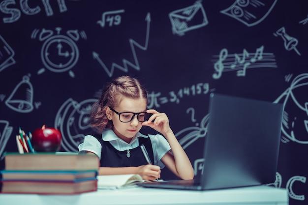 Piccola studentessa con gli occhiali che studia con il fondo della lavagna della scuola di computer torna a scuola