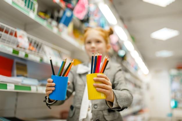 La piccola studentessa tiene gli occhiali con le matite, fa shopping in cartoleria