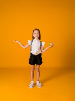 Una piccola scolaretta in uniforme e con uno zaino in piedi e tiene in mano una mela su uno sfondo giallo con una copia dello spazio