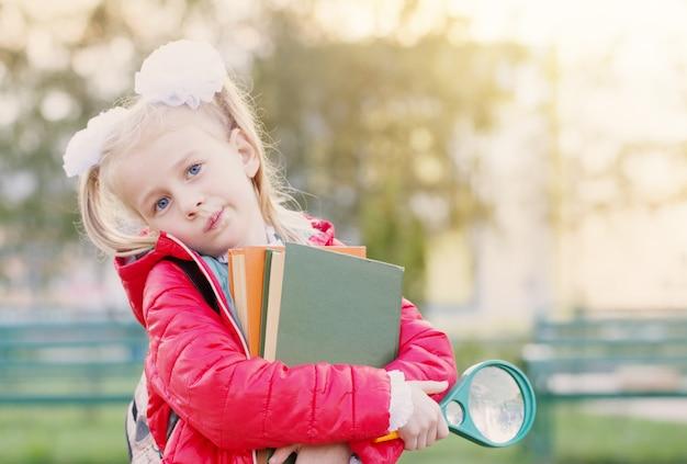 Piccola studentessa con libri in giacca rossa sulla scuola di sfondo