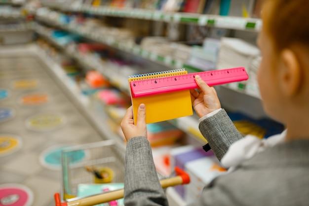 Piccola studentessa con un carrello che sceglie il taccuino, fa shopping in cartoleria