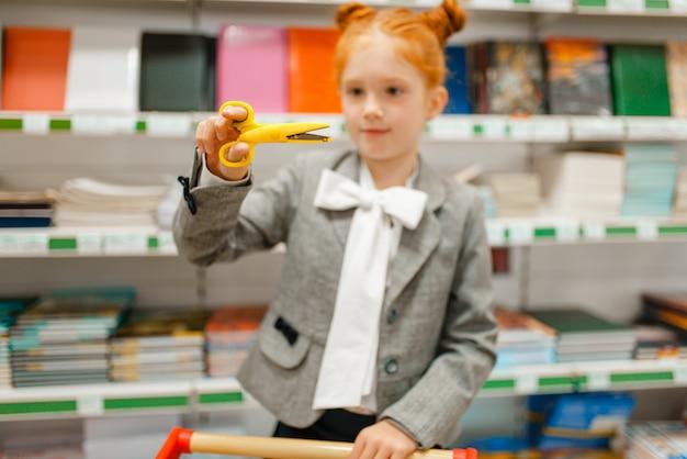 Piccola studentessa con un carrello che sceglie le forbici, fa la spesa in cartoleria
