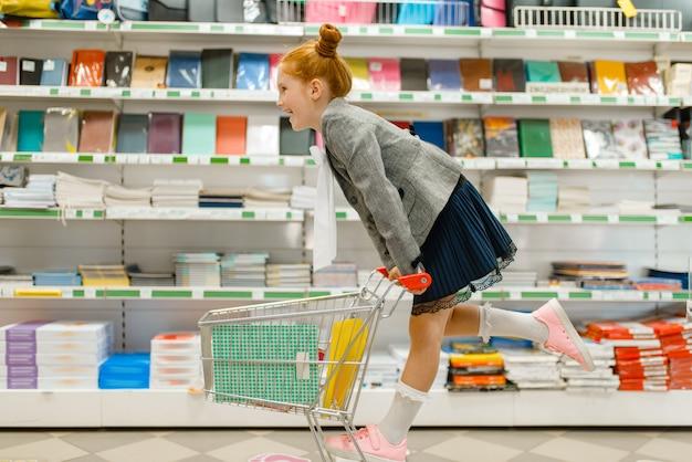 Piccola studentessa con un carrello allo scaffale, shopping in cartoleria. bambino femminile acquisto di forniture per ufficio in negozio, scolaro in supermercato