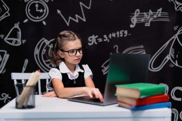 Piccola studentessa con gli occhiali che guarda al computer sullo sfondo della lavagna della scuola torna a scuola