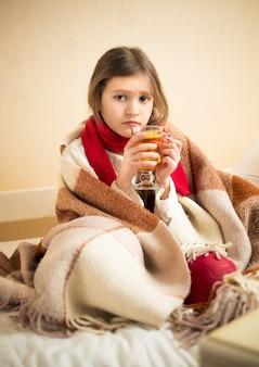 Piccola ragazza malata che copre in plaid e tiene una tazza di tè