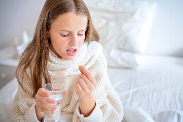 Una bambina malata sta per ingoiare una pillola.