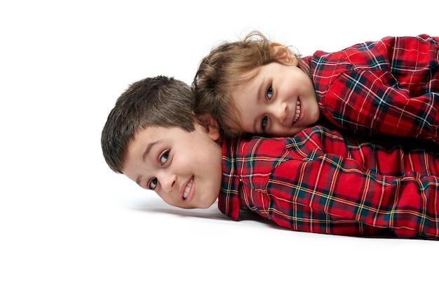 La sorellina è sdraiata sopra suo fratello accanto alle scatole con i regali