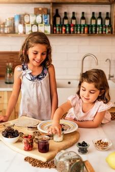 Ragazza delle sorelline che prepara i biscotti di cottura. concetto di chef infantile.