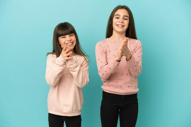 Sorelline ragazze isolate su sfondo blu che applaudono dopo la presentazione in una conferenza