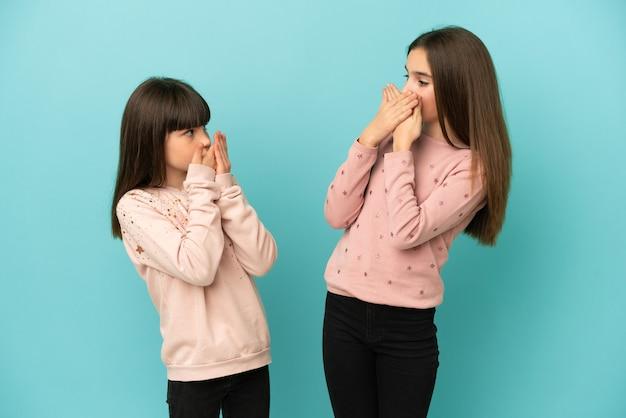 Sorelline isolate su sfondo blu che coprono la bocca con le mani per aver detto qualcosa di inappropriato