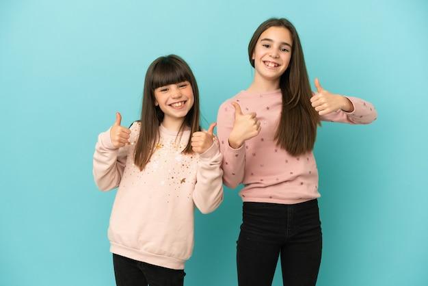 Sorelline isolate su sfondo blu che danno un gesto di pollice in alto con entrambe le mani e sorridono