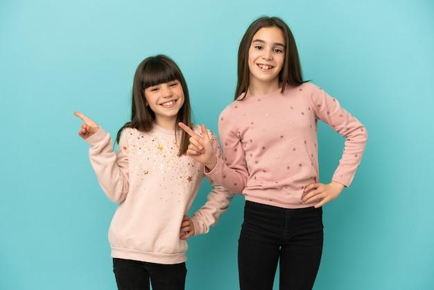 Sorelline ragazze isolate su sfondo blu che puntano il dito sul lato e presentano un prodotto