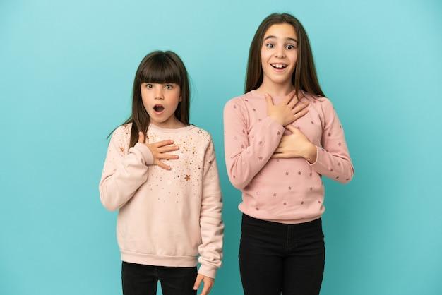 Piccole sorelle ragazze isolate su sfondo blu sorprese e scioccate mentre guardavano a destra