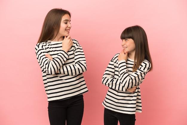 Sorelline ragazze isolate su sfondo rosa che si guardano l'un l'altro