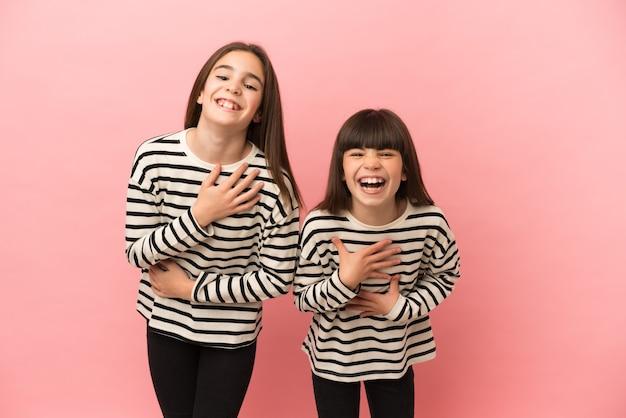 Sorelline ragazze isolate su sfondo rosa che sorridono molto mentre mettono le mani sul petto