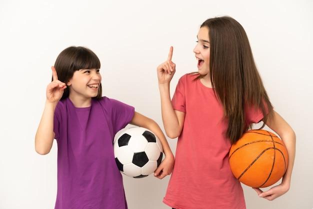 Sorelline che giocano a calcio e basket isolate con l'intenzione di realizzare la soluzione mentre alzano un dito