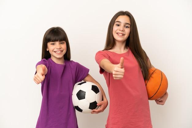 Piccole sorelle che giocano a calcio e basket isolato su sfondo bianco dando un pollice in alto gesto perché è successo qualcosa di buono