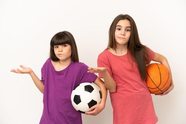 Piccole sorelle che giocano a calcio e basket isolati su sfondo bianco che hanno dubbi mentre si alzano le mani e le spalle