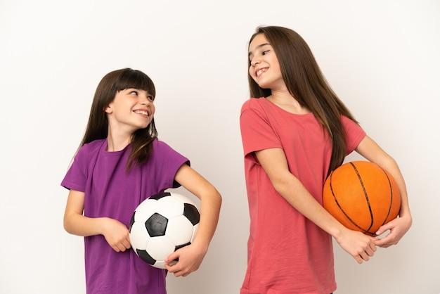 Piccole sorelle che giocano a calcio e basket isolato su sfondo bianco guardando sopra la spalla con un sorriso