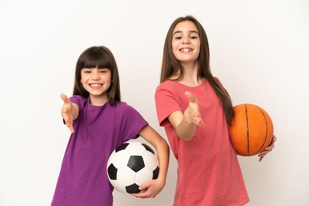 Piccole sorelle che giocano a calcio e basket isolato su sfondo bianco si stringono la mano per chiudere un buon affare