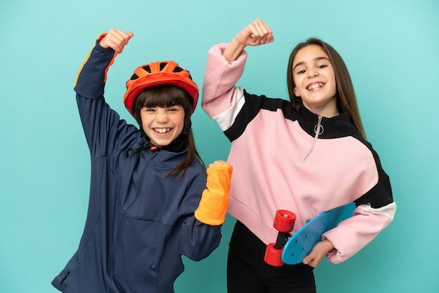 Piccole sorelle che praticano ciclismo e pattinatore isolato su sfondo blu che celebra una vittoria