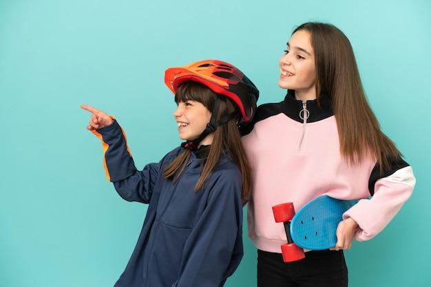Sorelline che praticano ciclismo e pattinatore isolato su sfondo blu che presentano un'idea mentre guardano sorridendo verso