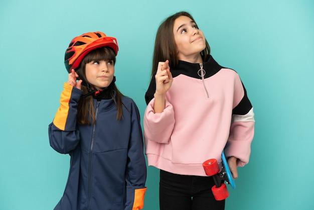 Piccole sorelle che praticano ciclismo e pattinatore isolato su sfondo blu con le dita che si incrociano e che desiderano il meglio