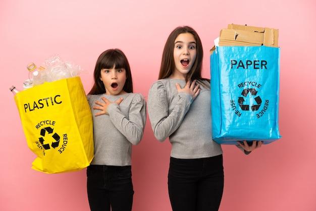 Sorelline che riciclano carta e plastica isolate su sfondo rosa sorprese e scioccate mentre guardavano a destra