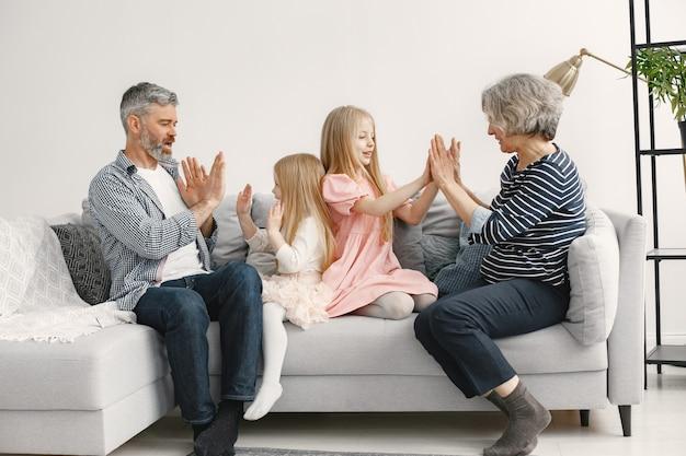 Sorelline sedute sul divano con i nonni.
