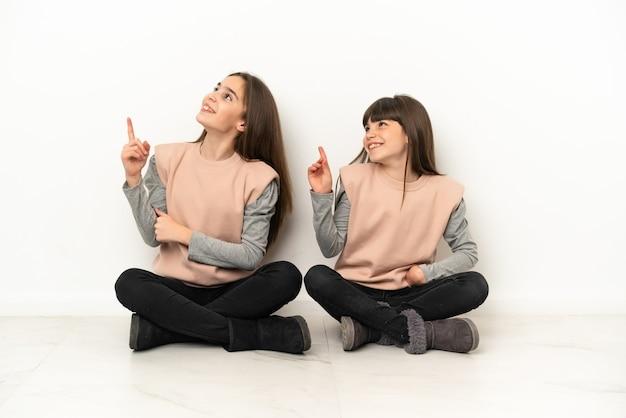 Sorelline sedute sul pavimento isolate indicando una grande idea e guardando in alto