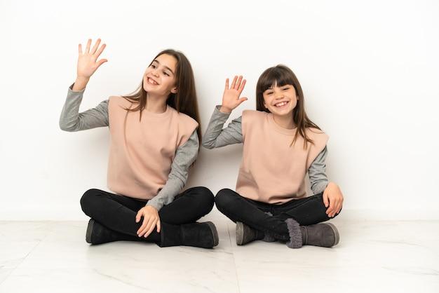 Piccole sorelle che si siedono sul pavimento isolate su fondo bianco che salutano con la mano con l'espressione felice