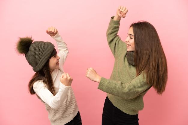 Sorelline che indossano abiti invernali isolati su sfondo rosa che celebrano una vittoria nella posizione del vincitore