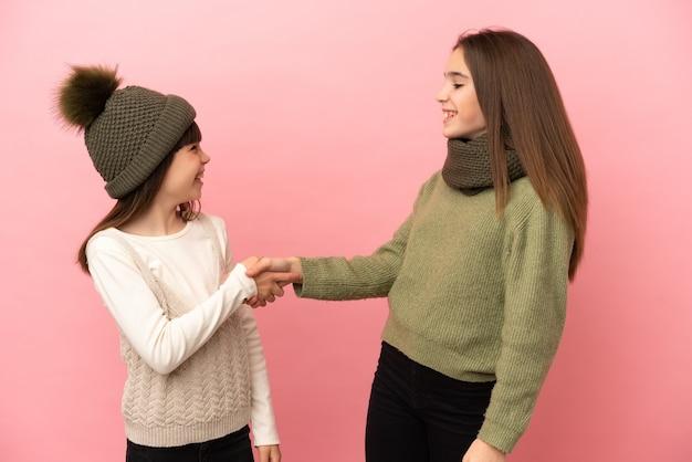 Sorelline che indossano abiti invernali isolati su sfondo rosa che si stringono la mano dopo un buon affare