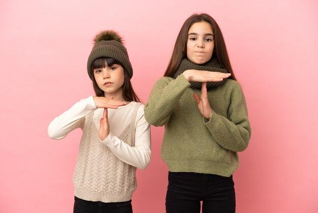 Piccole sorelle che indossano un abbigliamento invernale isolato su sfondo rosa che fa il gesto di arresto con la mano per fermare un atto