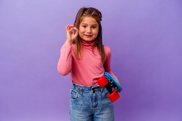Piccola ragazza caucasica del pattinatore isolata su fondo blu allegro e sicuro che mostra gesto giusto.