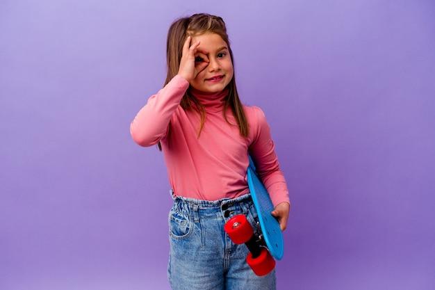 La piccola ragazza caucasica del pattinatore isolata su fondo blu ha eccitato mantenendo il gesto giusto sull'occhio.