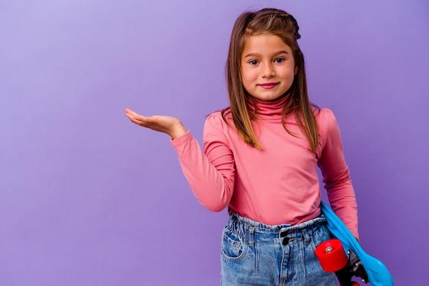 Piccola ragazza caucasica pattinatrice isolata su sfondo blu che mostra uno spazio di copia su un palmo e tiene un'altra mano sulla vita.
