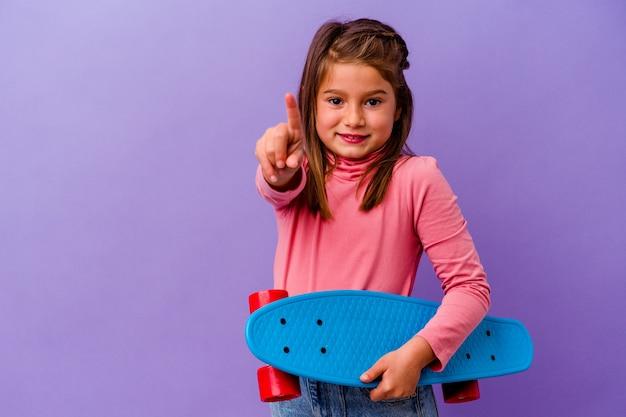 Ragazza caucasica del piccolo pattinatore isolata sull'azzurro che mostra il numero uno con il dito.