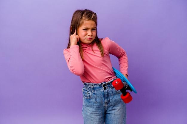 Piccola ragazza del pattinatore isolata sulle orecchie del rivestimento murale blu con le mani
