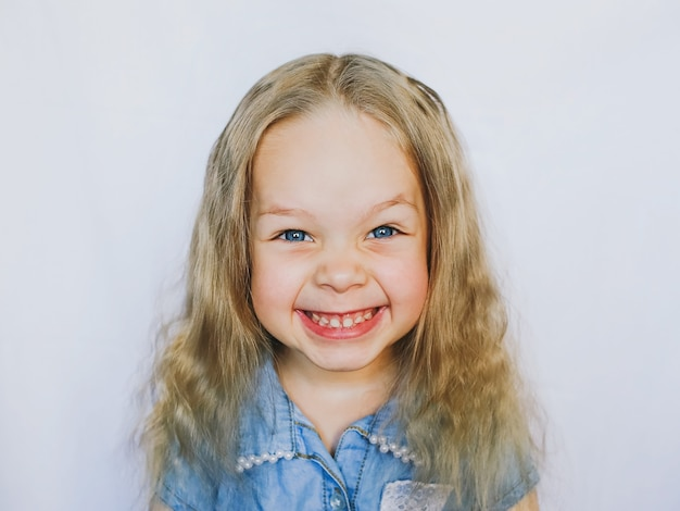 Bambina sorridente con gli occhi azzurri bella, su uno sfondo bianco