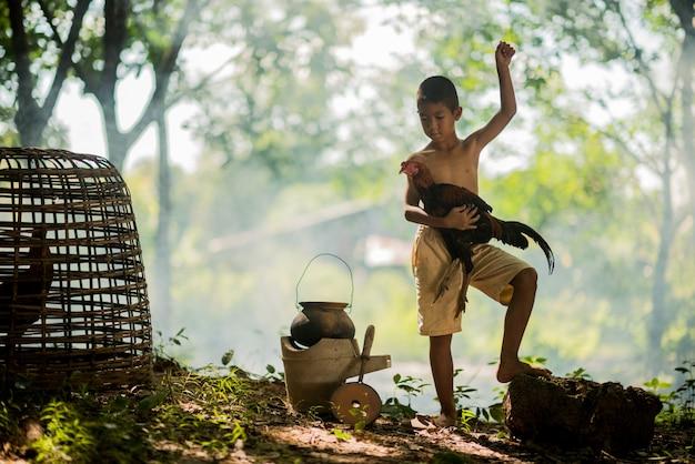Piccolo ragazzo e gallo sorridenti sulla foresta verde in campagna