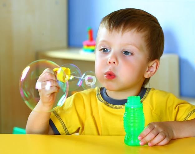 Il piccolo ragazzo sorridente sta giocando con le bolle di sapone.