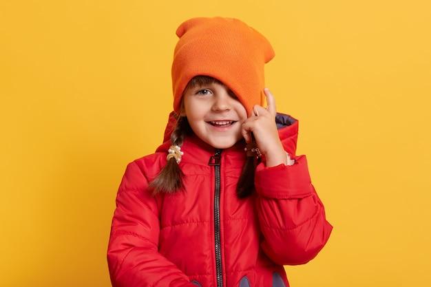 Piccola bambina sorridente che indossa in giacca rossa casual e cappello arancione, guarda la parte anteriore con felice espressione