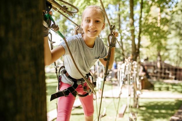 La piccola ragazza sorridente in attrezzatura si arrampica nel parco della corda