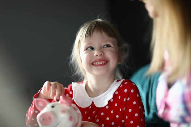 La piccola ragazza sorridente tiene il porcellino salvadanaio con la moneta in sua mano