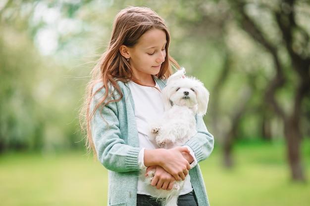 Piccola ragazza sorridente che gioca e che abbraccia cucciolo nel parco