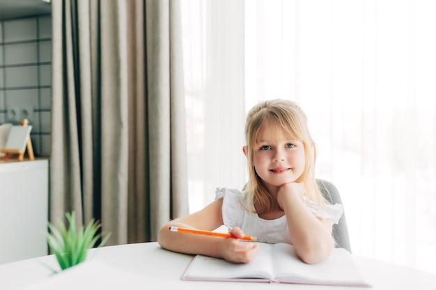 Una bambina sorridente si siede al tavolo e scrive su un taccuino bianco. concetto di educazione. istruzione domiciliare. compiti a casa. faccia sorridente. foto di alta qualità